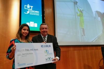 """Thaís venceu o concurso com a foto """"Aproveitando a água da chuva"""". Ela recebeu o prêmio do vice-presidente diretor do CNA, José Mário Shreiner""""."""