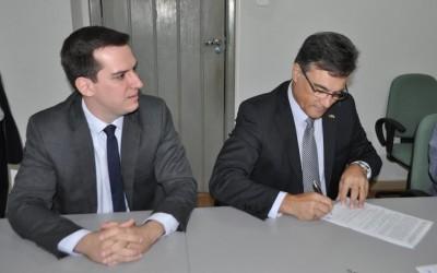 Ingo Kobarg Júnior, (BB) assina na presença de assessores.
